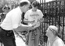 Dr. Ron Sable (left) speaks with activist David Bell (right), who had chained himself to the fence of Gov. Jim Thompson's home to protest draconian state AIDS legislation in 1987. Hundreds of people marched on Thompson's home. Both Sable and Bell later died of AIDS. Photo from Outlines archives.