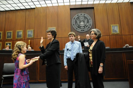 Judge James F. Holderman (back) administers the oath for Mary Rowland, surrounded by her children Lilly and Thomas and wife Julie Justicz. Photos by Hal Baim