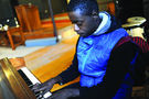 Koala, 18, plays piano inside C3. During Sunday dinners, youth regularly take turns playing the church's instruments. Photo by Bill Healy.