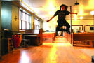 One young person leaps for the camera after a Sunday dinner at C3. Photo by Kate Sosin.